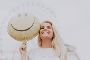 happy woman with smiley balloon